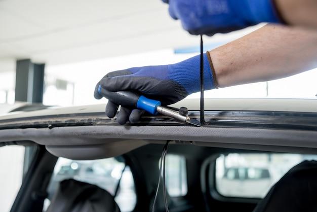 Specjalni pracownicy samochodów usuwają starą szybę przednią lub szybę samochodową w garażu stacji obsługi samochodów.