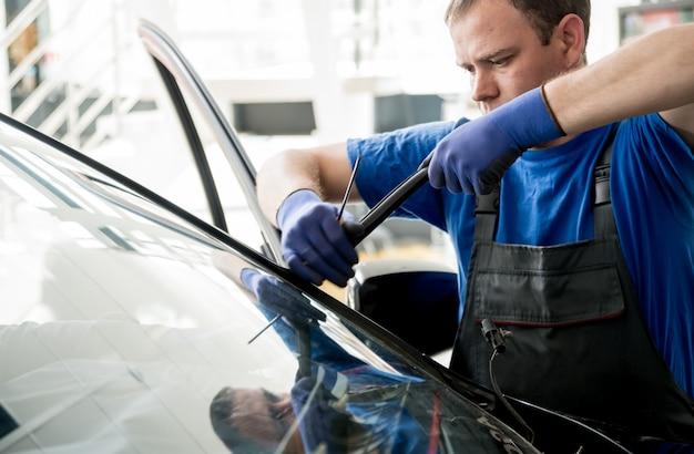 Specjalni pracownicy samochodowi usuwają starą przednią szybę lub szybę samochodu w warsztacie samochodowym.