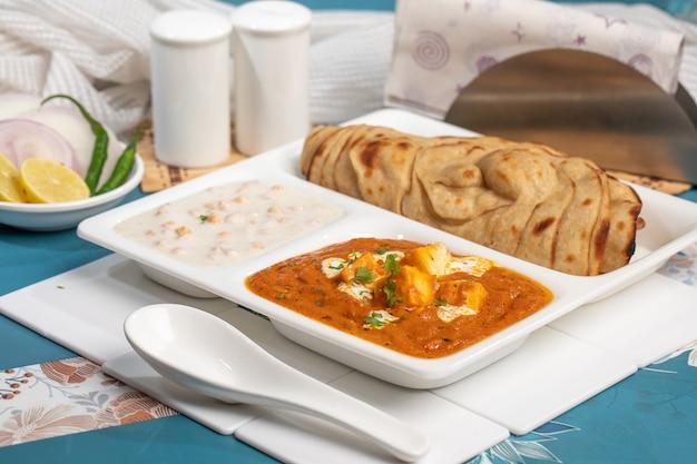 Specjalności kuchni indyjskiej danie z kuchni indyjskiej czyli małe thali, warzywo paneer, rayata i laccha paratha