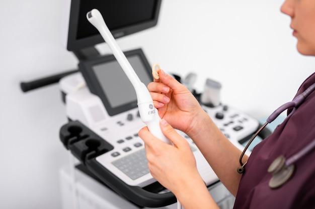 Specjalny czujnik ultradźwiękowy nowoczesnego skanera ultradźwiękowego do kontroli dopochwowej i małej prezerwatywy medycznej w rękach lekarza młodej kobiety przygotowującej się do skanu urządzenia.