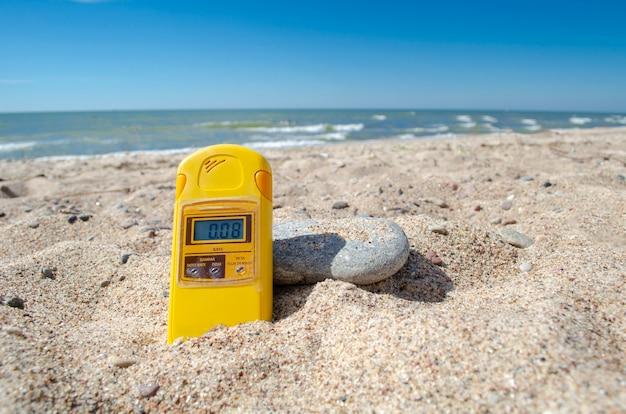 Specjalny dozymetr promieniowania na piasku nad brzegiem morza