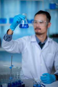 Specjalny młody naukowiec lub badacz badający roztwór chemiczny przez probówkę do eksperymentu szczepionkowego opracowywanego w nowoczesnym laboratorium biologicznym