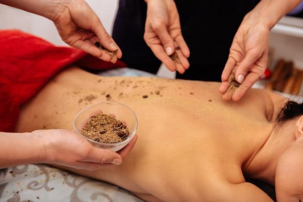 Specjalny proszek. mistrzowie w salonie nakładają peeling z ziaren kawy na plecy, aby uzyskać gładszą skórę