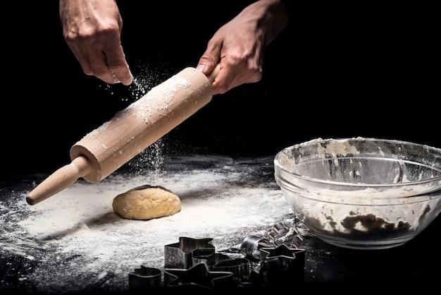 Specjalny sprzęt. zbliżenie młodych mans ręce za pomocą wałka do ciasta podczas wyrabiania ciasta i gotowania