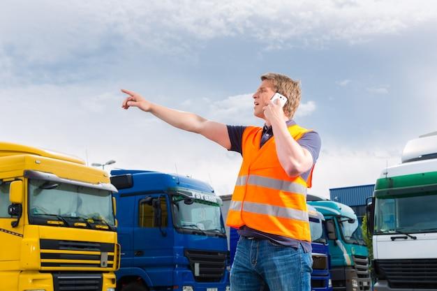 Spedytor przed ciężarówkami na zajezdni