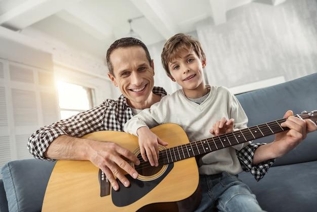Spędzać razem czas. przystojny, wesoły jasnowłosy chłopak, ucząc się gry na gitarze, siedząc na kanapie i uśmiechając się jego ojciec