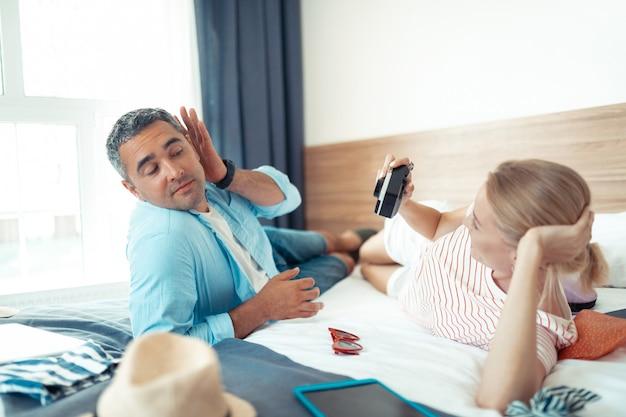 Spędzać razem czas. szczęśliwa kobieta leżąc na łóżku ze swoim śmiesznym mężem robi mu zdjęcia.