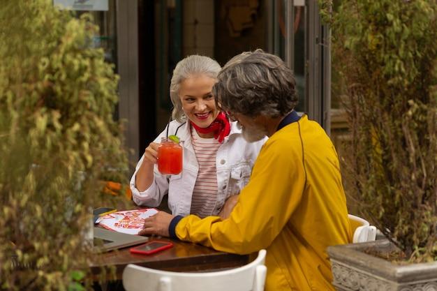 Spędzać razem czas. wesoła para dorosłych siedzi razem w kawiarni ulicy, picia i przygotowania do spaceru.