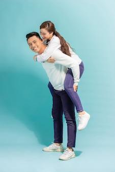 Spędzać razem wspaniały czas. szczęśliwy młody człowiek niosący swoją piękną dziewczynę na ramionach i uśmiechnięty stojąc