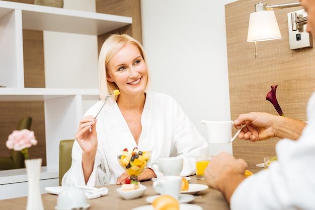 Spędzam wspaniały poranek. blondynki promieniejąca kobieta z owocami na widelcu, podczas gdy jej partner dodaje kremy do swojej kawy