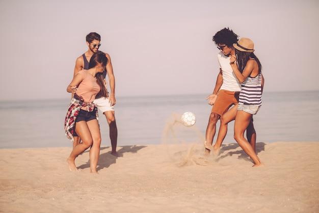 Spędzanie czasu z najlepszymi przyjaciółmi. grupa wesołych młodych ludzi bawiących się piłką nożną na plaży z morzem w tle