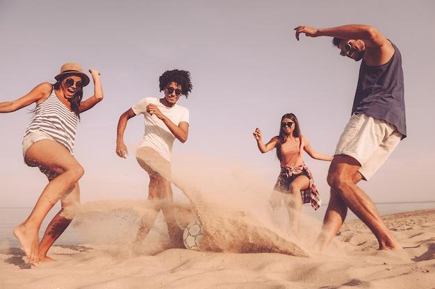 Spędzanie wspaniałego czasu z przyjaciółmi. grupa wesołych młodych ludzi bawiących się piłką nożną na plaży