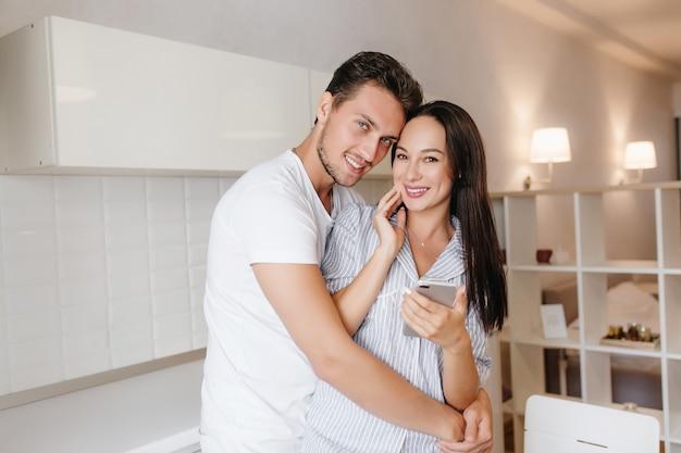 Spektakularna brunetka kobieta z komórką w ręku, pozowanie w ramionach męża z uśmiechem