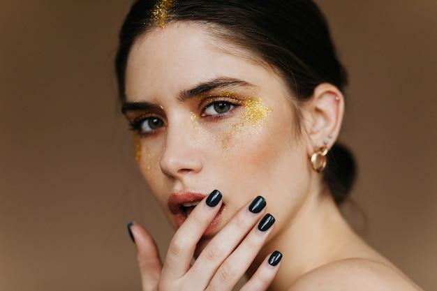 Spektakularna czarnowłosa kobieta z zainteresowaniem. z bliska strzał oszałamiająca brunetka dziewczyna z makijażem strony.