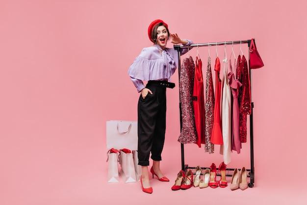 Spektakularna dama w czarnych spodniach zalotnie unosi nogę i po zakupach trzyma torebkę na różowym tle z paczkami.