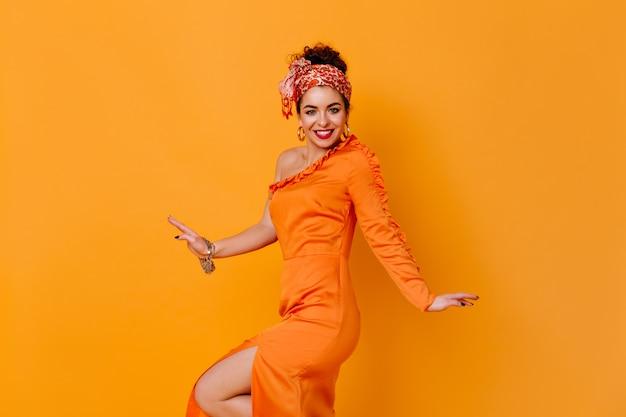 Spektakularna dama w niezwykłej opasce i satynowej sukience z rozcięciem uśmiecha się na pomarańczowej przestrzeni.
