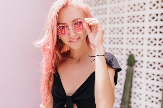 Spektakularna kobieta o opalonej skórze dotykająca okularów przeciwsłonecznych i delikatnie się uśmiechająca.
