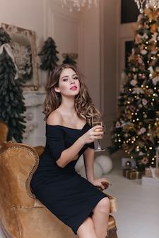 Spektakularna kręcona brązowowłosa kobieta w dopasowanej czarnej sukience siedzi na welurowym beżowym krześle i delektuje się lampką smacznego szampana w noworocznej atmosferze.
