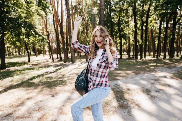Spektakularna młoda dama w dżinsach tańczy w letnim lesie. beztroska dziewczyna z plecakiem wygłupia się podczas plenerowej sesji zdjęciowej.