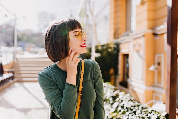 Spektakularna młoda kobieta uśmiechnięta spacerując po mieście w dobry, ciepły dzień. zewnątrz portret beztroskiej modelki z prostymi czarnymi włosami.