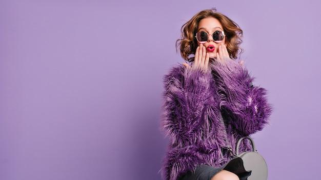 Spektakularna młoda kobieta z modnym makijażem pozuje z zaskoczonym wyrazem twarzy na jasnym fioletowym tle