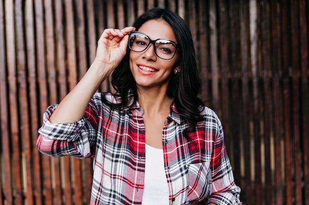 Spektakularna opalona kobieta, figlarnie dotykająca okularów na drewnianej ścianie. urocza dama z uśmiechniętą falującą fryzurą.