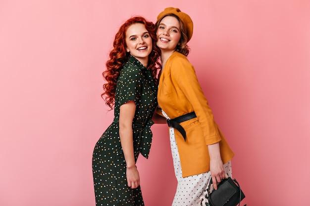 Spektakularne dziewczyny pozują razem na różowym tle. studio strzałów pięknych pań patrząc na kamery z uśmiechem.