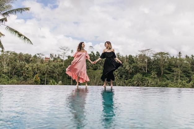 Spektakularne kobiety bawiące się jej sukienkami podczas pozowania nad jeziorem. pełnometrażowy odkryty strzał kobiet trzymających się za ręce na naturze.