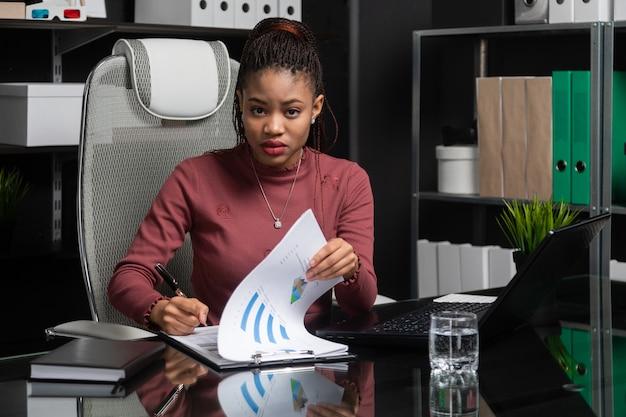 Spektakularny młody czarny bizneswoman podpisuje dokumenty przy stole w biurze