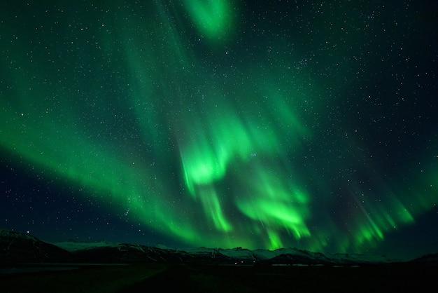 Spektakularny pokaz zorzy polarnej w nocy nad górami, spektakularna zorza polarna i nocna gwiazda na islandii