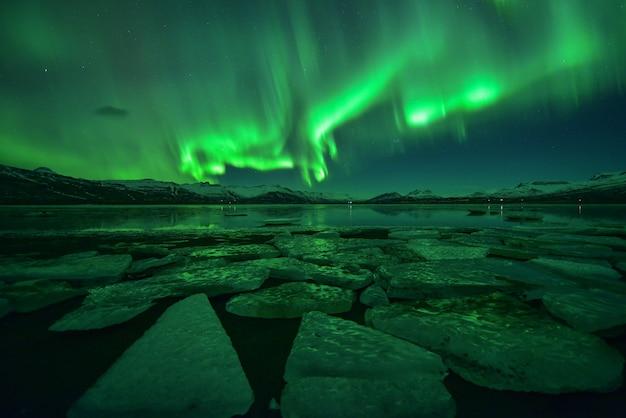 Spektakularny pokaz zorzy polarnej w nocy nad lodowym morzem na islandii