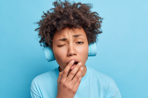 Śpiąca afroamerykanka czuje się znudzona, uczy się obcych słów, słuchając ścieżek dźwiękowych przez słuchawki, ziewa i zakrywa usta, ubrana niedbale, na tle niebieskiej ściany. pojęcie zmęczenia