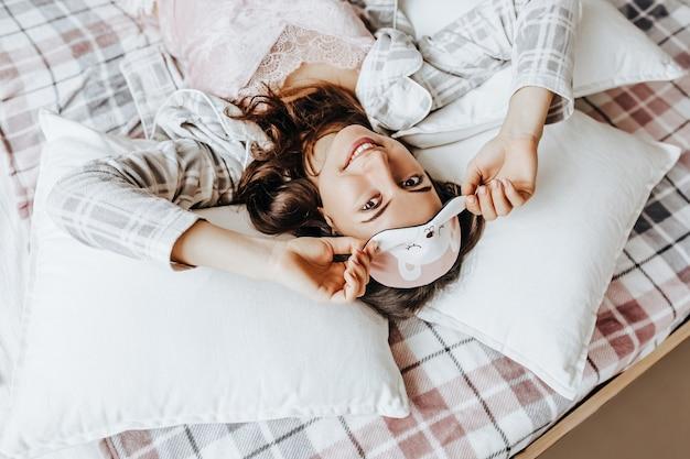 Śpiąca brunetka leży w łóżku z zawiązanymi oczami, budząc się rano