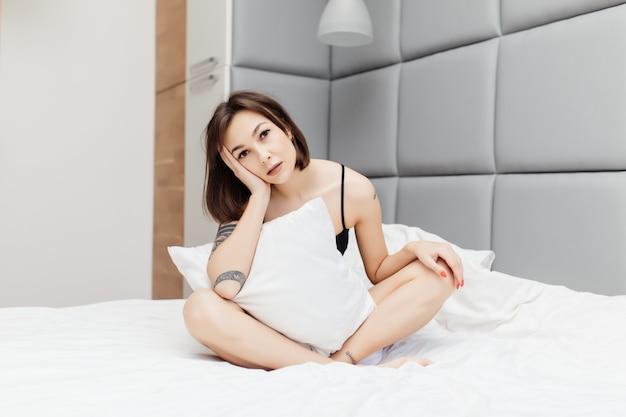 Śpiąca brunetka pokazuje niezdrowe spojrzenie rano w swoim szerokim łóżku