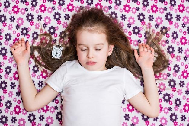 Śpiąca dziewczyna i biały budzik. widok z góry