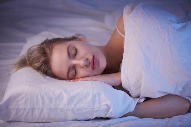 Śpiąca dziewczyna na poduszce z nocnym oświetleniem