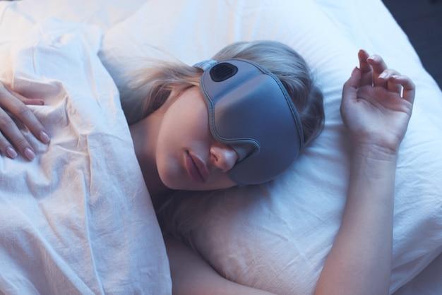 Śpiąca dziewczyna w masce snu na poduszce z nocnym oświetleniem