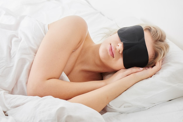 Śpiąca dziewczyna w masce snu na poduszce