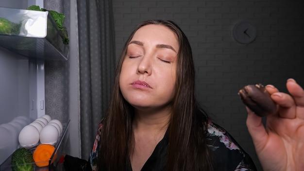 Śpiąca głodna kobieta je z apetytem pyszne ciasto czekoladowe z półki w ciemnej kuchni w nocy z bliska widok z wnętrza lodówki