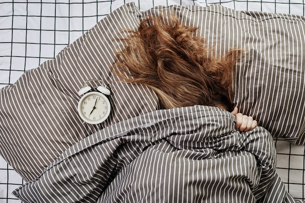 Śpiąca kobieta pod kocem w łóżku i vintage budzik na poduszce. leniwy poranek i koncepcja pobudki