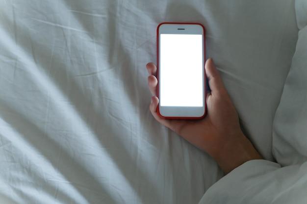 Śpiąca kobieta pod kocem z telefonem w ręku.