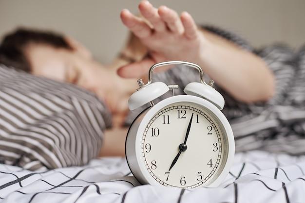 Śpiąca kobieta w sypialni i rocznika budzik