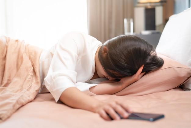 Śpiąca kobieta wyłącza alarm na smartfonie podczas snu w łóżku