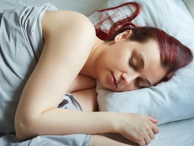 Śpiąca kobieta z rudymi włosami leży w łóżku z zamkniętymi oczami, poranne słońce pada na jej twarzśpiąca kobieta z rudymi włosami leży w łóżku z zamkniętymi oczami, poranne słońce pada na jej twarz
