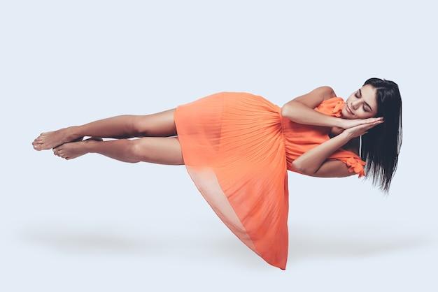 Śpiąca królewna. pełnej długości strzał studio atrakcyjnej młodej kobiety w pomarańczowej sukience, unoszącej się w powietrzu i trzymającej zamknięte oczy