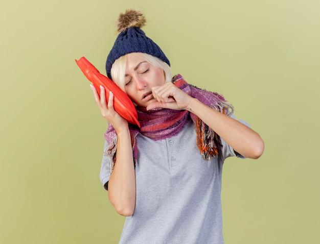 Śpiąca młoda blondynka chora słowiańska kobieta w czapce zimowej i szaliku kładzie głowę na butelce z gorącą wodą, trzymając pięść blisko twarzy odizolowaną na oliwkowej ścianie z miejscem na kopię