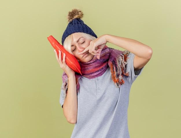 Śpiąca młoda blondynka chora słowiańska kobieta w czapce zimowej i szaliku ociera nos palcem i kładzie głowę na butelce z gorącą wodą odizolowaną na oliwkowej ścianie z miejscem na kopię