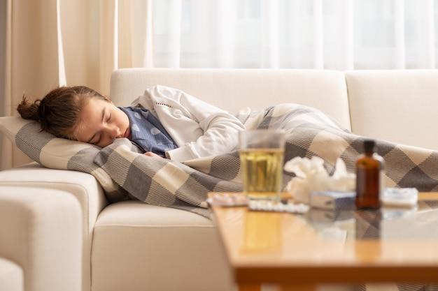 Śpiąca młoda chora dziewczyna leżąca na kanapie z przeziębieniem i wysoką gorączką.