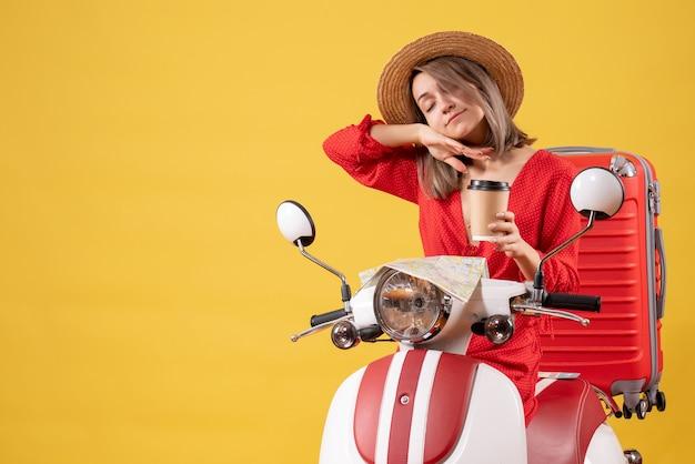 Śpiąca młoda dama w czerwonej sukience trzymająca filiżankę kawy w pobliżu motoroweru