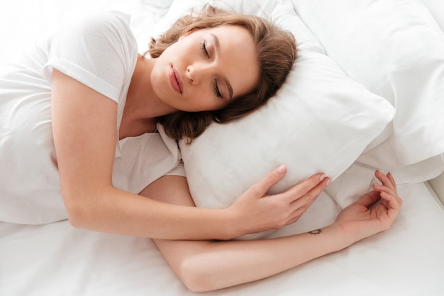 Śpiąca młoda kobieta leży w łóżku z zamkniętymi oczami.